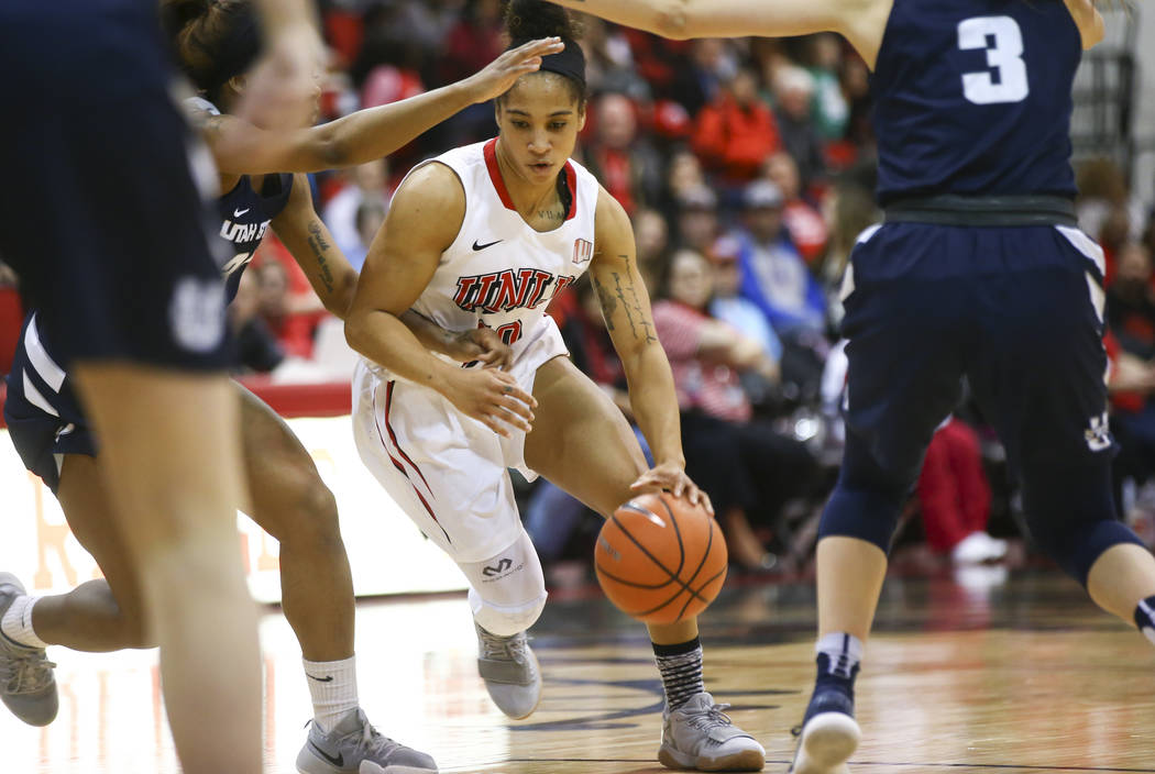 UNLV Lady Rebels guard Nikki Wheatley (10) drives against Utah State Aggies guards Victoria Price, left and Olivia West (3) during the first half of a basketball game at the Cox Pavilion in Las Ve ...
