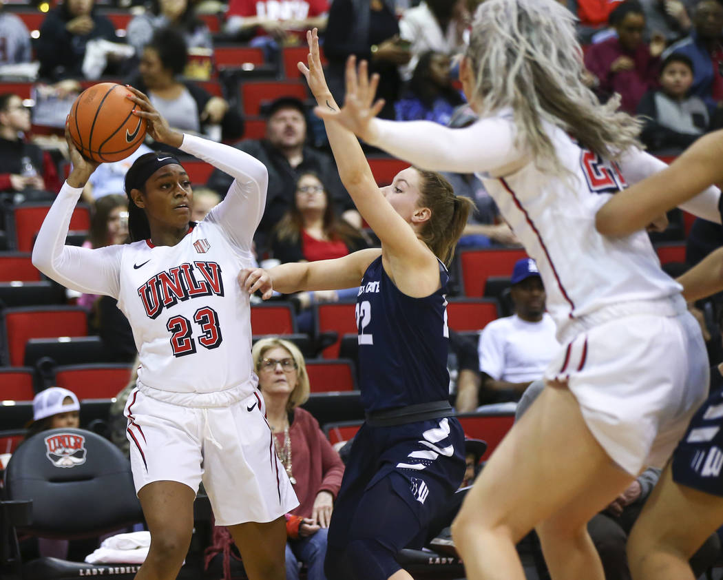 UNLV Lady Rebels forward Jordyn Bell (23) looks to pass as Utah State Aggies guard Rachel Brewster (22) defends during the first half of a basketball game at the Cox Pavilion in Las Vegas on Frida ...