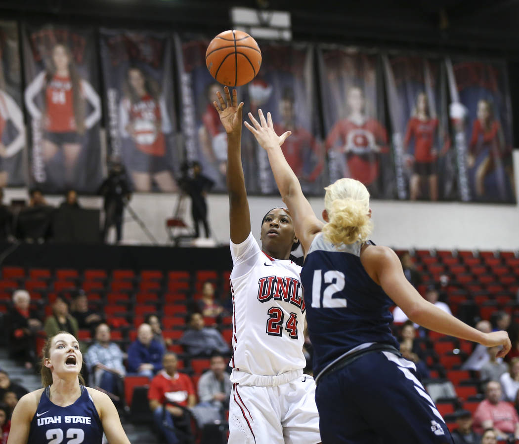 UNLV Lady Rebels center Rodjanae Wade (24) shoots over Utah State Aggies guard/forward Hailey Bassett (12) during the first half of a basketball game at the Cox Pavilion in Las Vegas on Friday, Ma ...
