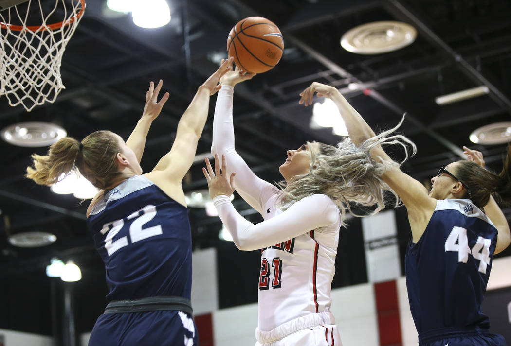 UNLV Lady Rebels forward/center Katie Powell (21) goes to the basket between Utah State Aggies guard Rachel Brewster (22) and center Deja Mason (44) during the second half of a basketball game at  ...