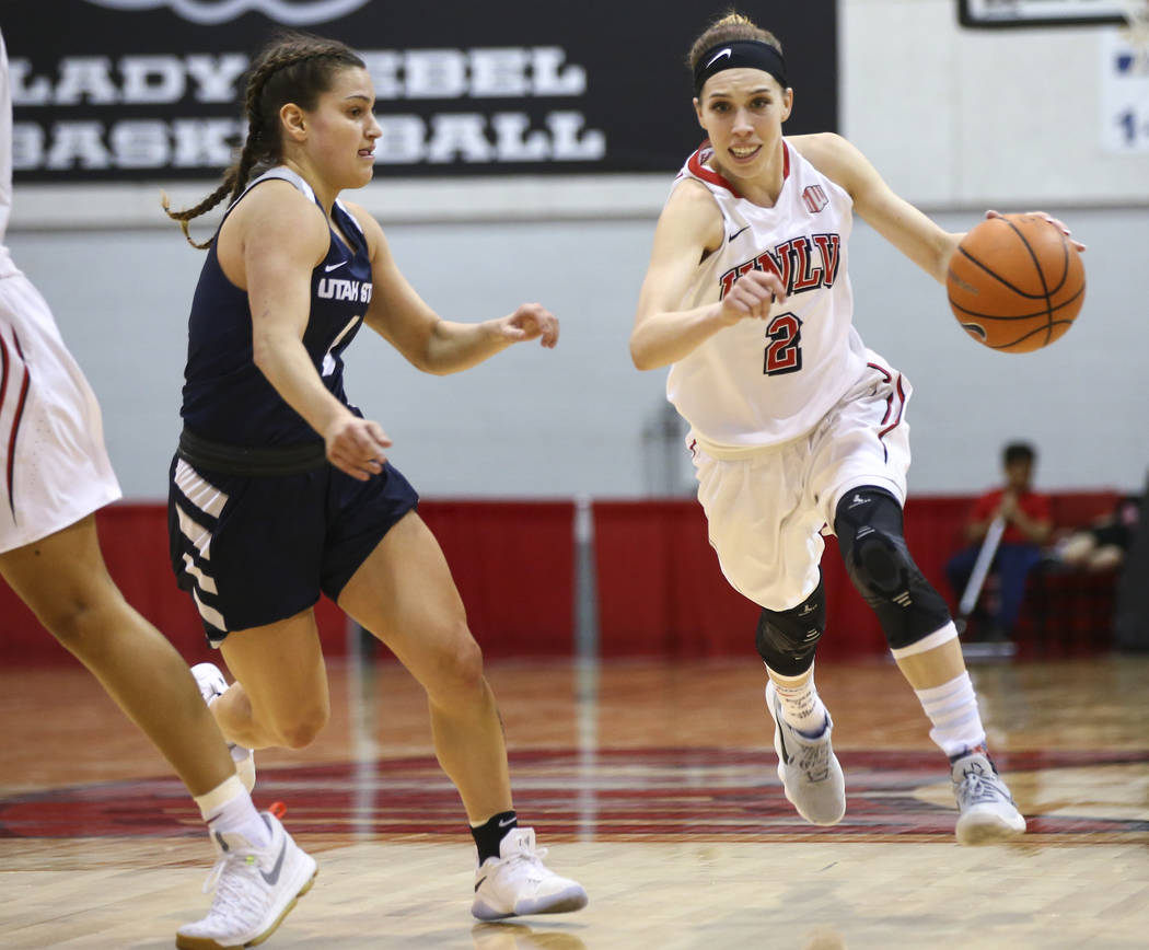 UNLV Lady Rebels guard Brooke Johnson (2) drives against Utah State Aggies guard Eliza West (1) during the second half of a basketball game at the Cox Pavilion in Las Vegas on Friday, March 2, 201 ...