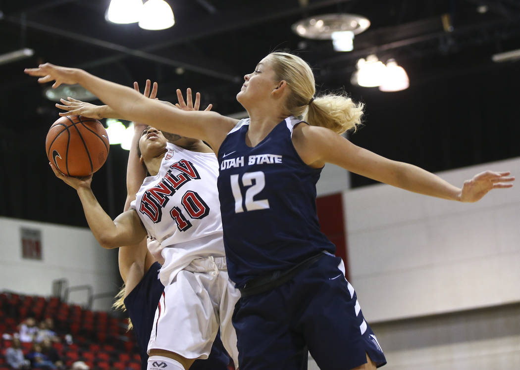 Utah State Aggies guard/forward Hailey Bassett (12) defends as UNLV Lady Rebels guard Nikki Wheatley (10) goes to the basket during the second half of a basketball game at the Cox Pavilion in Las  ...