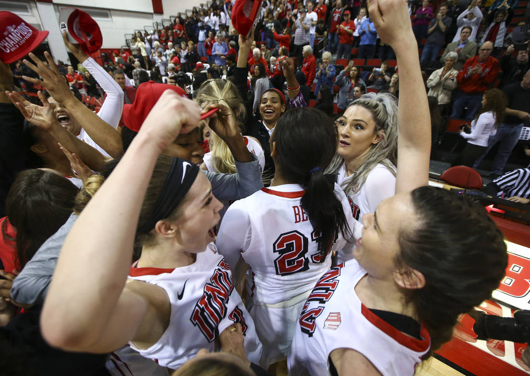 UNLV Lady Rebels players, including guard Brooke Johnson, left, and forward Alyssa Anderson (20), right, celebrate their regular season Mountain West championship win after defeating Utah State at ...