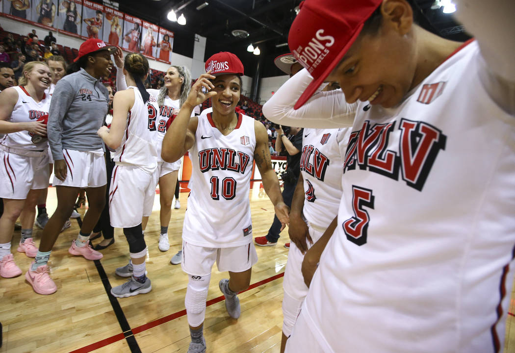 UNLV Lady Rebels guard Nikki Wheatley (10) and forward Simone Sheppard (5) put on hats to  celebrate their regular season Mountain West championship win after defeating Utah State at the Cox Pavil ...