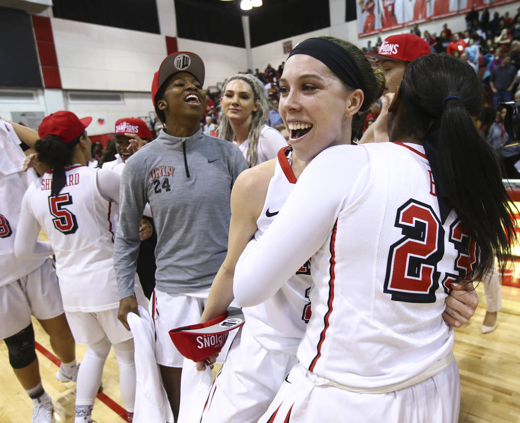UNLV Lady Rebels guard Brooke Johnson, center, and forward Jordyn Bell (23) celebrate their regular season Mountain West championship win after defeating Utah State at the Cox Pavilion in Las Vega ...