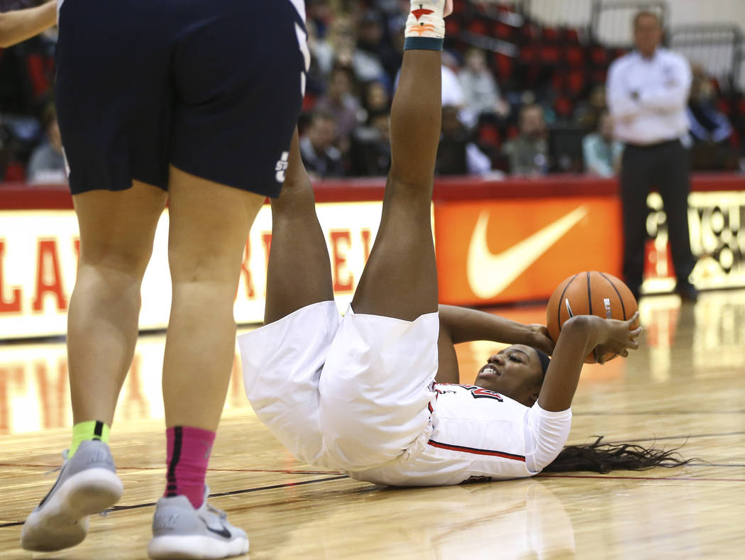 UNLV Lady Rebels center Rodjanae Wade (24) looks to pass as she falls to the ground during the second half of a basketball game against the Utah State Aggies at the Cox Pavilion in Las Vegas on Fr ...
