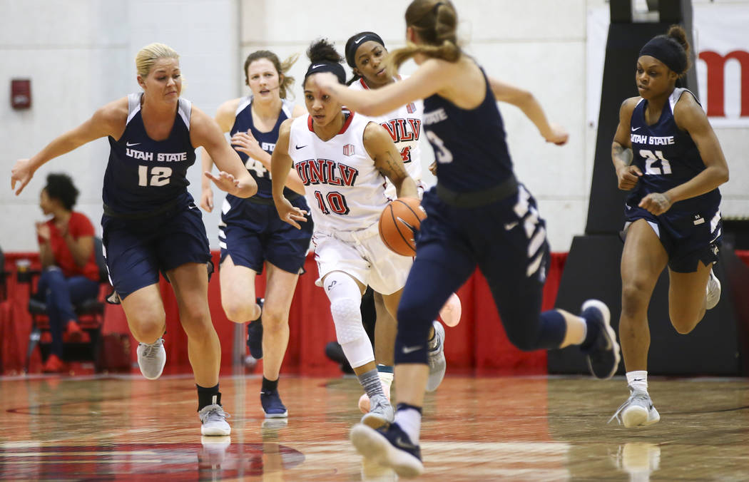UNLV Lady Rebels guard Nikki Wheatley (10) brings the ball up court past Utah State Aggies guard/forward Hailey Bassett (12) during the first half of a basketball game at the Cox Pavilion in Las V ...