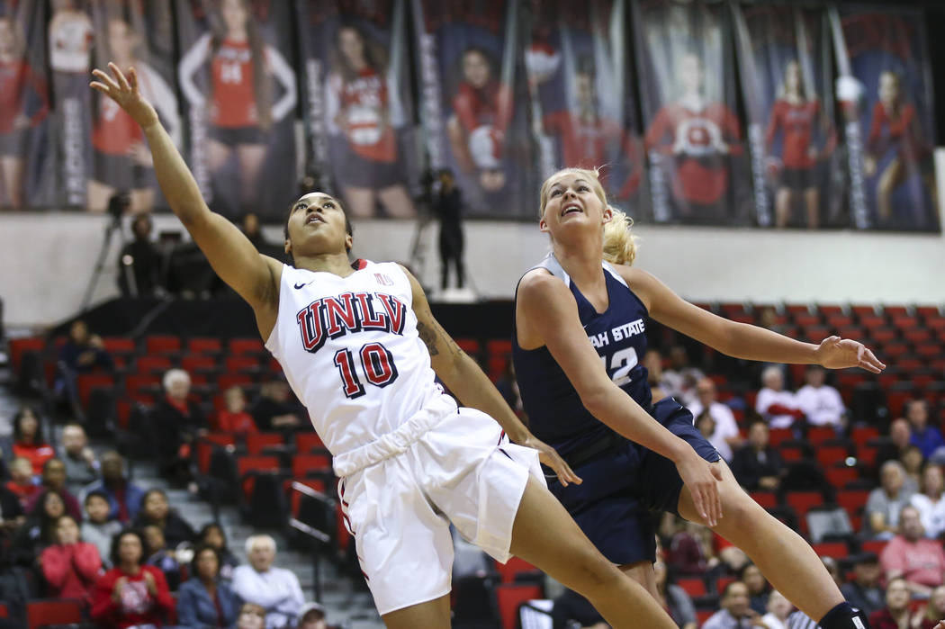 UNLV Lady Rebels guard Nikki Wheatley (10) sends up a shot past Utah State Aggies guard/forward Hailey Bassett (12) during the first half of a basketball game at the Cox Pavilion in Las Vegas on F ...