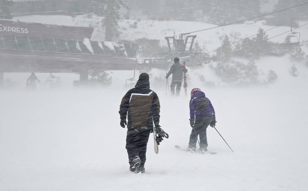In this photo provided by Northstar California, a snowboarder and pair of skiers make their way through gusts of wind to a lift Thursday, March 1, 2018, at the Northstar California resort in Truck ...