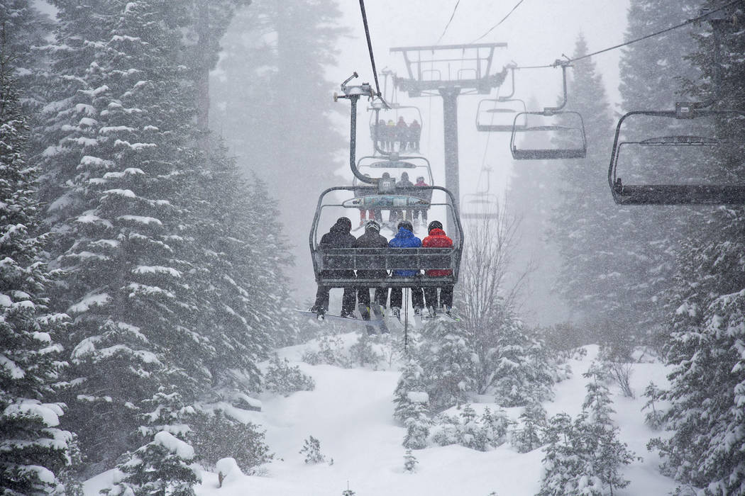 In this photo provided by Northstar California, skiers ride a chair lift as snow falls Thursday, March 1, 2018, at the Northstar California resort in Truckee, Calif. A major winter storm moved acr ...