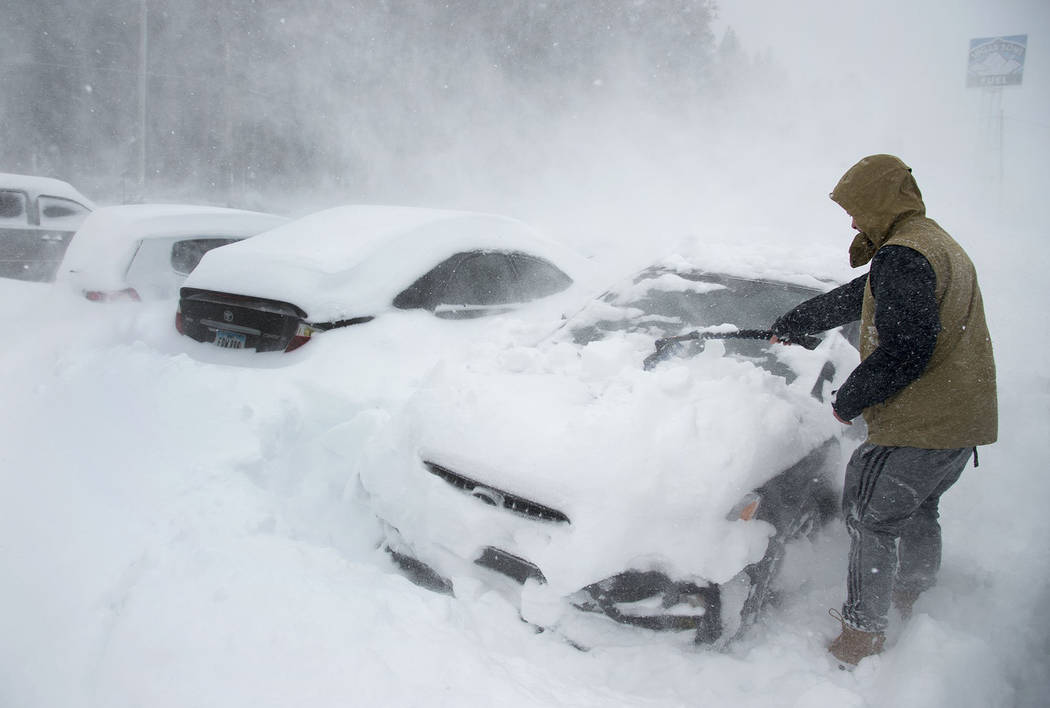 Heavy winds blow snow as Ryan Foster, 25, scrapes snow from his car in the parking lot where he lives at the Donner Summit Lodge in Norden on Thursday, March 1, 2018, near Donner Summit, Calif. A  ...