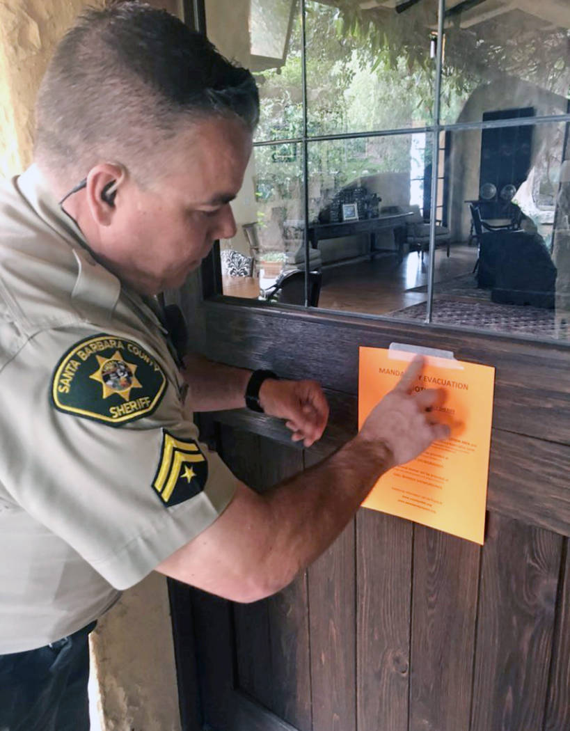 Santa Barbara County Sheriff's Deputy Mike Harris posts a notice on a home near Carpinteria, Calif., advising of the mandatory evacuation notice due to forecast rain and possible debris flow due t ...