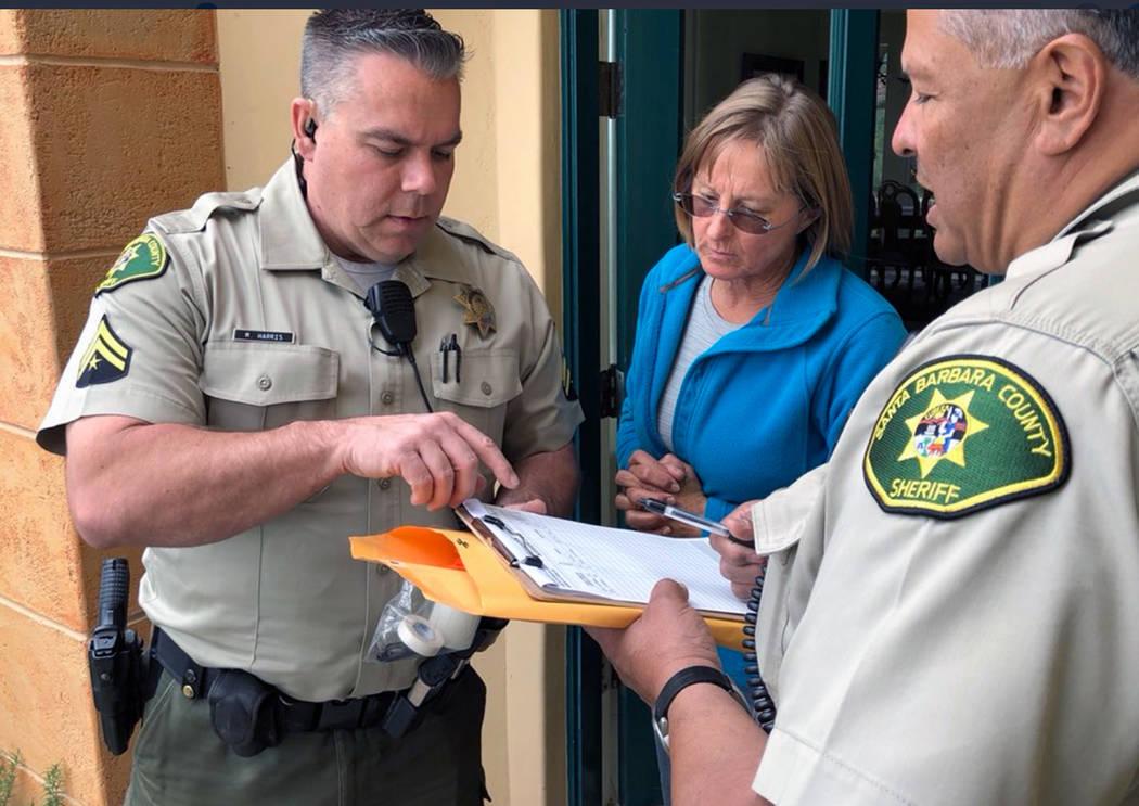 Santa Barbara County Sheriff's Deputies Mike Harris, left, and Noel Rivas talk with a resident near Carpinteria, Calif., advising of the mandatory evacuation notice due to forecast rain and possib ...