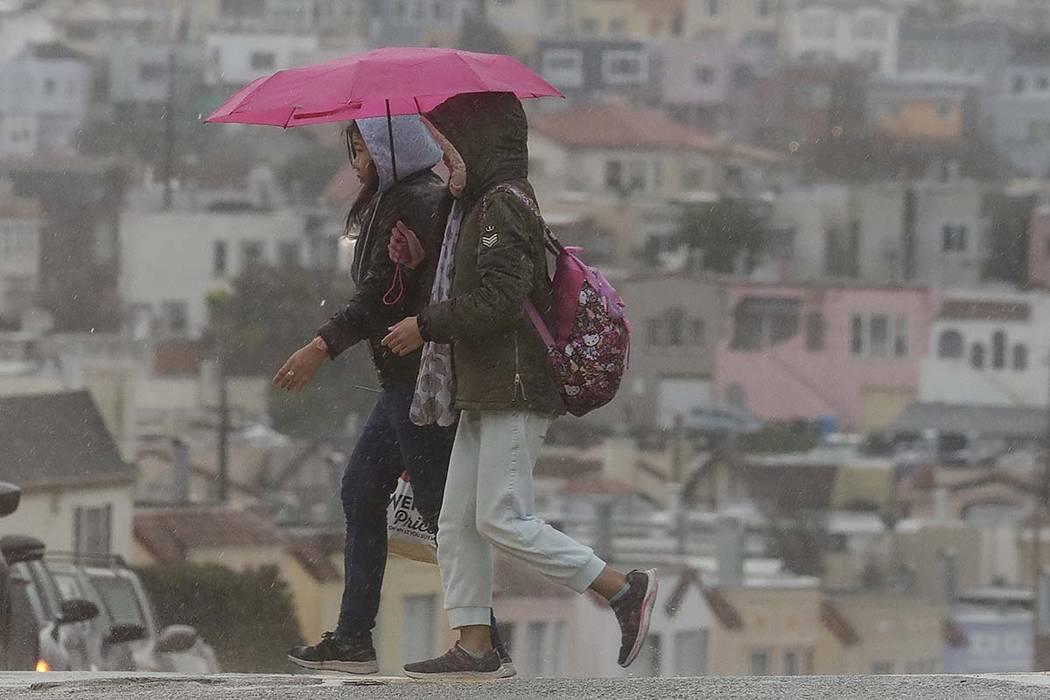 A pedestrian walks with an umbrella as she crosses the