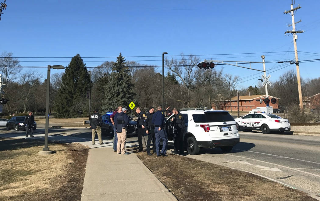 Authorities stand on the campus of Central Michigan University during a search for a suspect, in Mount Pleasant, Mich., Friday, March 2, 2018. School officials say police are responding to a repor ...