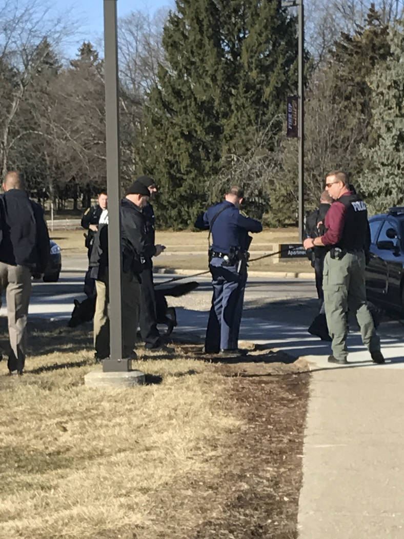 Authorities gather on the campus of Central Michigan University during a search for a suspect, in Mount Pleasant, Mich., Friday, March 2, 2018. School officials say police are responding to a repo ...