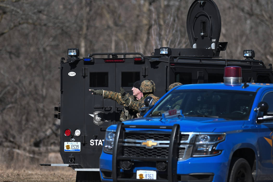 Law enforcement officers search a wooded area for a suspect involved in a shooting at a Central Michigan University residence hall on Friday, March 2, 2018 in Mt. Pleasant, Mich. (Matthew Dae Smit ...