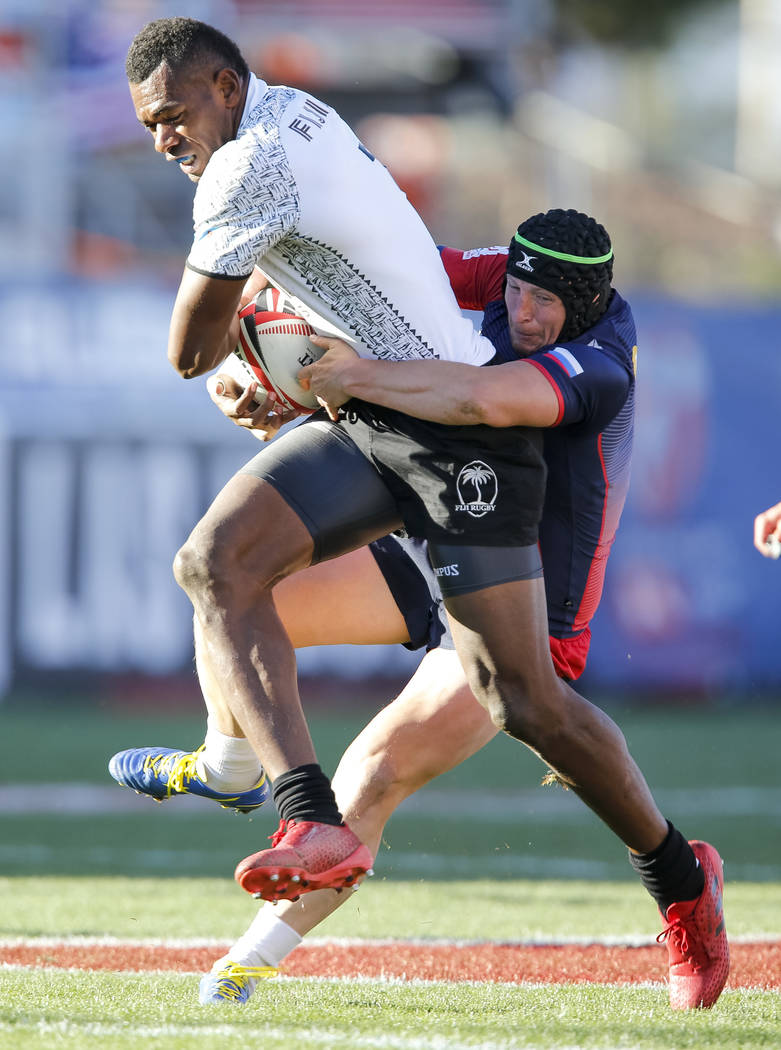 Mesulame Kunavula of Fiji runs the ball as Sergei Ianiushkin of Russia attempts to bring him down during day one of the USA Sevens Rugby tournament at Sam Boyd Stadium in Las Vegas on Friday, Marc ...