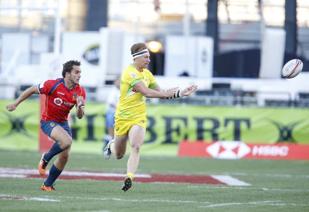 Ben O'Donnell of Australia passes the ball as Jacobo Martin of Spain closes in during day one of the USA Sevens Rugby tournament at Sam Boyd Stadium in Las Vegas on Friday, March 2, 2018. Richard  ...