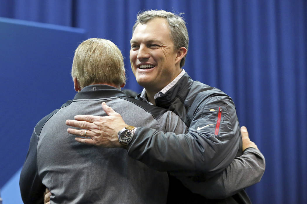San Francisco 49ers GM John Lynch is hugged by Oakland Raiders head coach Jon Gruden after winning the official coin flip to determine the 9th and 10th picks for the 2018 NFL Draft on Friday, Marc ...