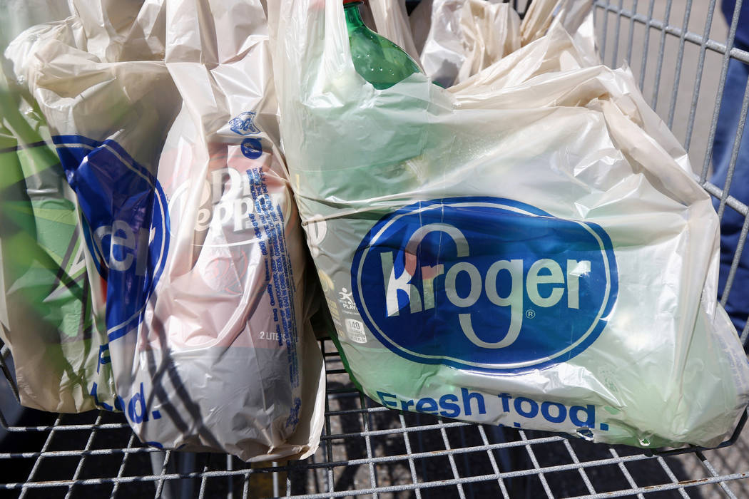In this June 15, 2017, photo, bagged purchases from the Kroger grocery store in Flowood, Miss., sit inside this shopping cart. Kroger said Thursday, March 1, that it's raising the minimum a ...