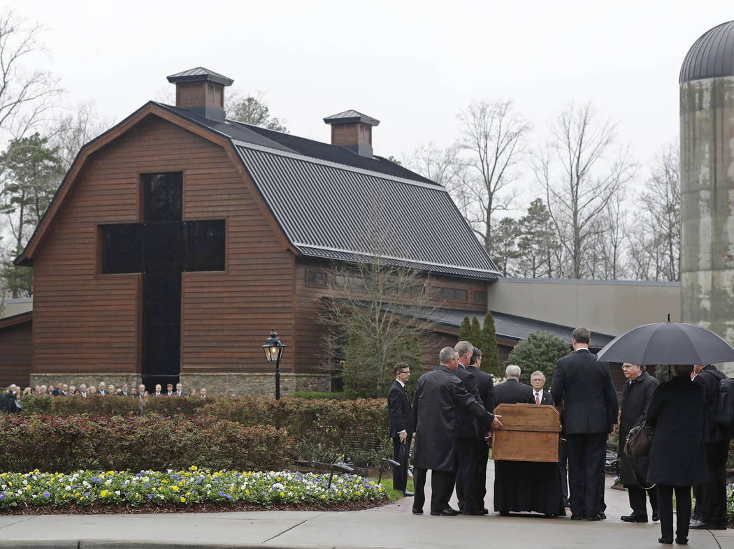 Pallbearers carry the casket of the Rev. Billy Graham past family members as it returns to the Billy Graham Library in Charlotte, N.C., Thursday, March 1, 2018. His funeral will be Friday. (AP Pho ...
