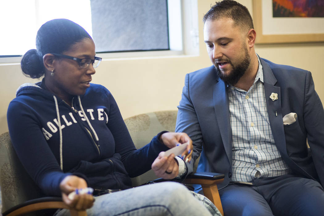 Chris Singer, vice president of Patient Experience at OptumCare, which oversees Southwest Medical, hands his business card to April J., 34, who visited the Oakey Healthcare Center with her mother, ...
