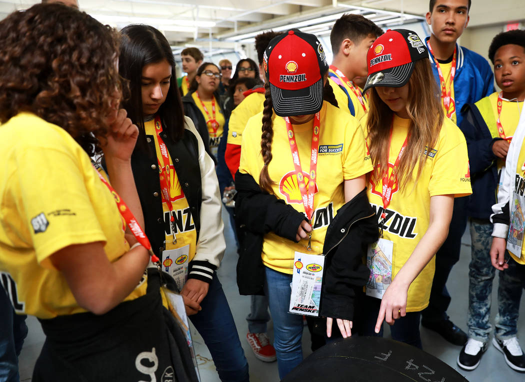 Jessica Leach, 14, right, touches a tire during a tour at the Goodyear building at the Las Vegas Motor Speedway in Las Vegas on Sunday, March 4, 2018. The 50 students won a contest to design, buil ...