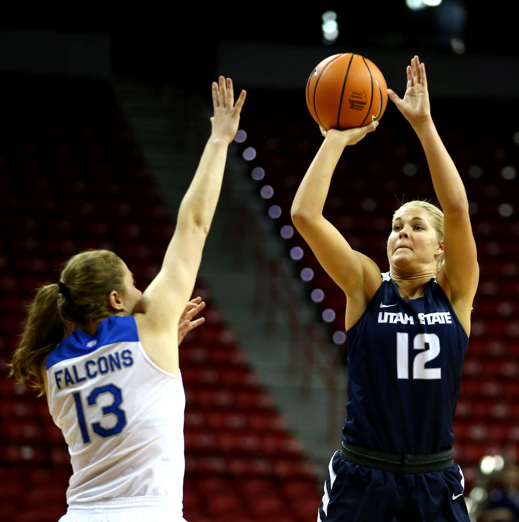 Utah State Aggies' Hailey Bassett (12) shoots against Air Force Falcons' Emily Conroe (13) during the Mountain West Conference tournament at the Thomas and Mack Center in Las Vegas on Monday, Marc ...