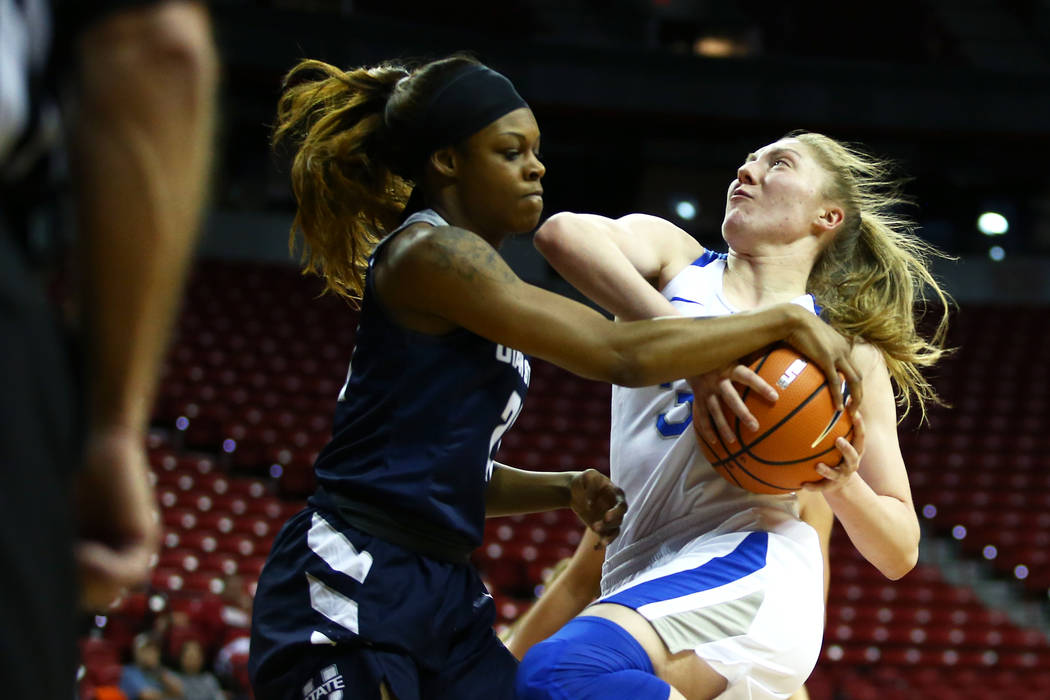 Air Force Falcons' Kaelin Immel (32) tries to shoot the ball against the Utah State Aggies' Victoria Price (21)during the Mountain West Conference tournament at the Thomas and Mack Center in Las V ...
