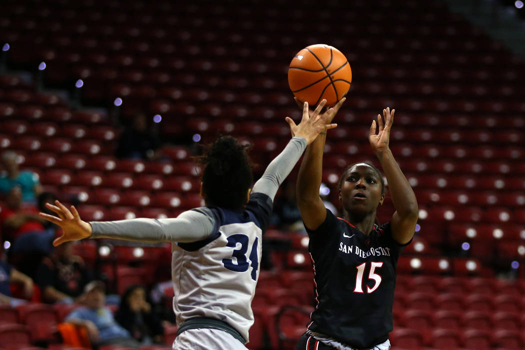 San Diego State Aztecs' McKynzie Fort (15) shoots against  Nevada Wolf Pack's Jade Redmon (34) during the Mountain West Conference tournament at the Thomas and Mack Center in Las Vegas on Monday,  ...