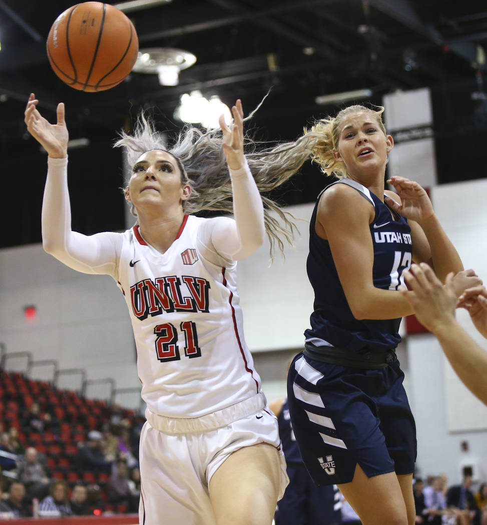 UNLV Lady Rebels forward/center Katie Powell (21) reaches for a rebound over Utah State Aggies guard/forward Hailey Bassett (12) during the second half of a basketball game at the Cox Pavilion in  ...