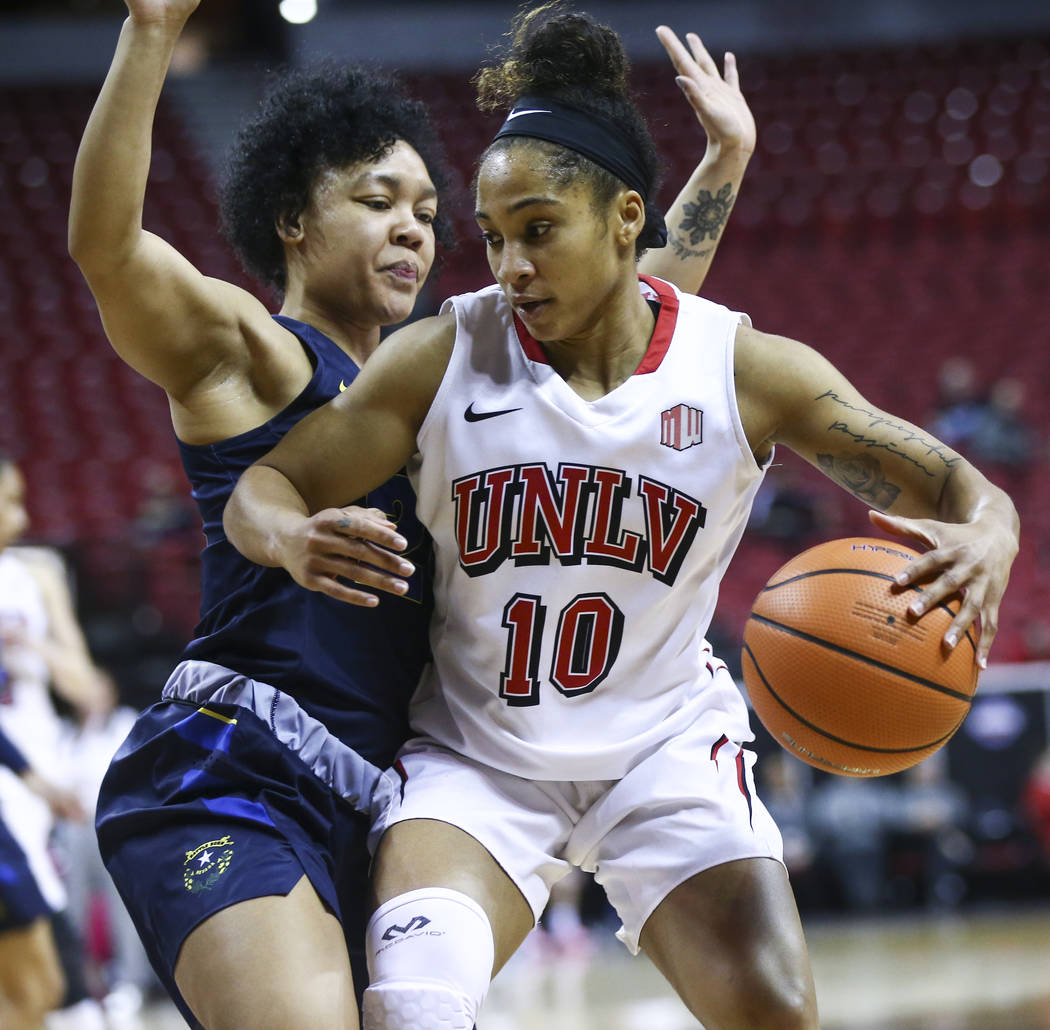UNLV Lady Rebels guard Nikki Wheatley (10) drives as UNR Wolf Pack guard Camariah King (24) defends during the first half of a basketball game in the Mountain West tournament quarterfinals at the  ...