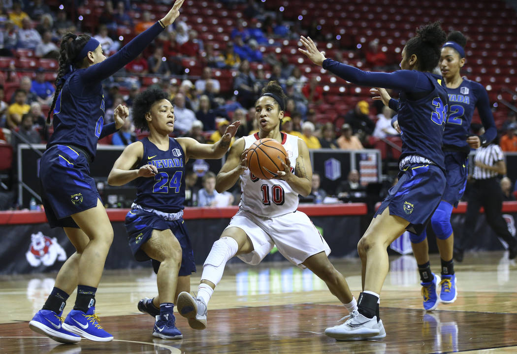 UNLV Lady Rebels guard Nikki Wheatley (10) drives between UNR Wolf Pack guards Camariah King (24) and Jade Redmon, right, during the second half of a basketball game in the Mountain West tournamen ...