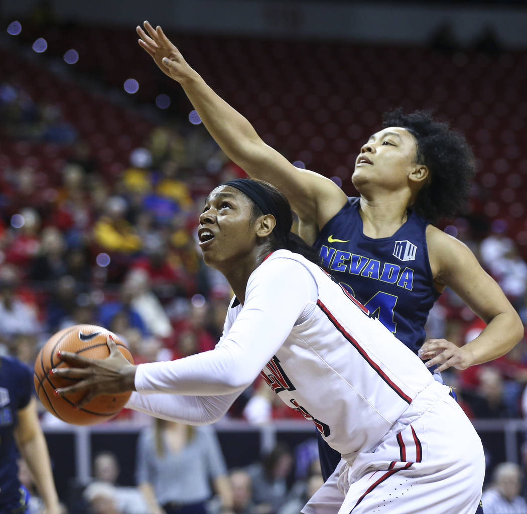 UNLV Lady Rebels forward Jordyn Bell (23) looks to shoot as UNR Wolf Pack guard Camariah King (24) defends during the first half of a basketball game in the Mountain West tournament quarterfinals  ...