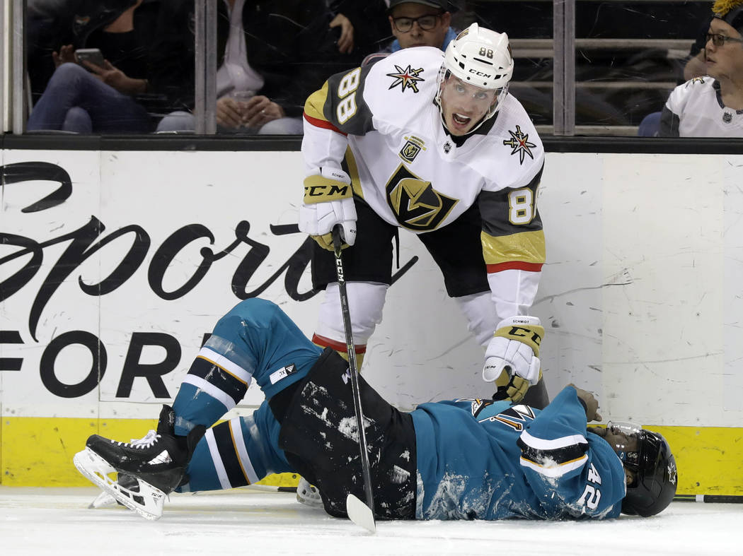 Vegas Golden Knights' Nate Schmidt, top, reaches down to San Jose Sharks' Joel Ward after they both collided during the second period of an NHL hockey game Thursday, Feb. 8, 2018, in San Jose, Cal ...