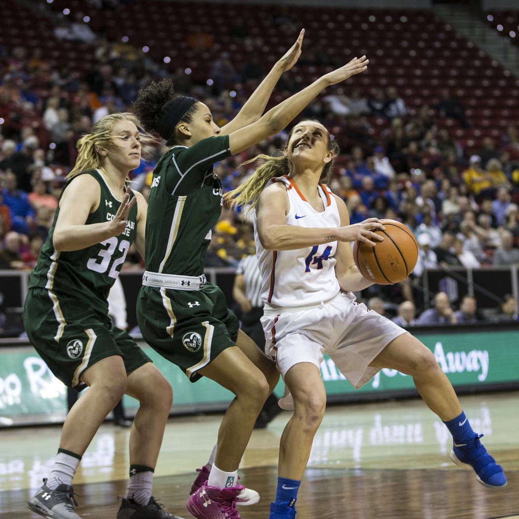 Boise State Broncos guard Braydey Hodgins (14) looks for an open shot under pressure from Colorado State Rams guard Jordyn Edwards (4) and forward Annie Brady (32) in the first half of the Mountai ...