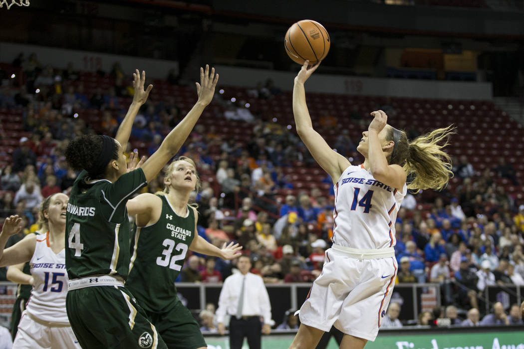Boise State Broncos guard Braydey Hodgins (14) takes a shot under pressure from Colorado State Rams guard Jordyn Edwards (4) and forward Annie Brady (32) in the first half of the Mountain West Con ...