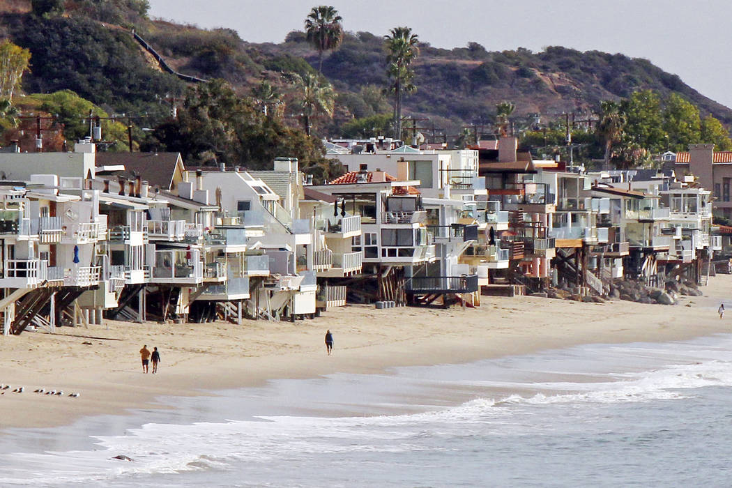 Waves roll up to and under homes perched over a sandy beach in Malibu, Calif., in 2015.  (AP Photo/John Antczak, file)