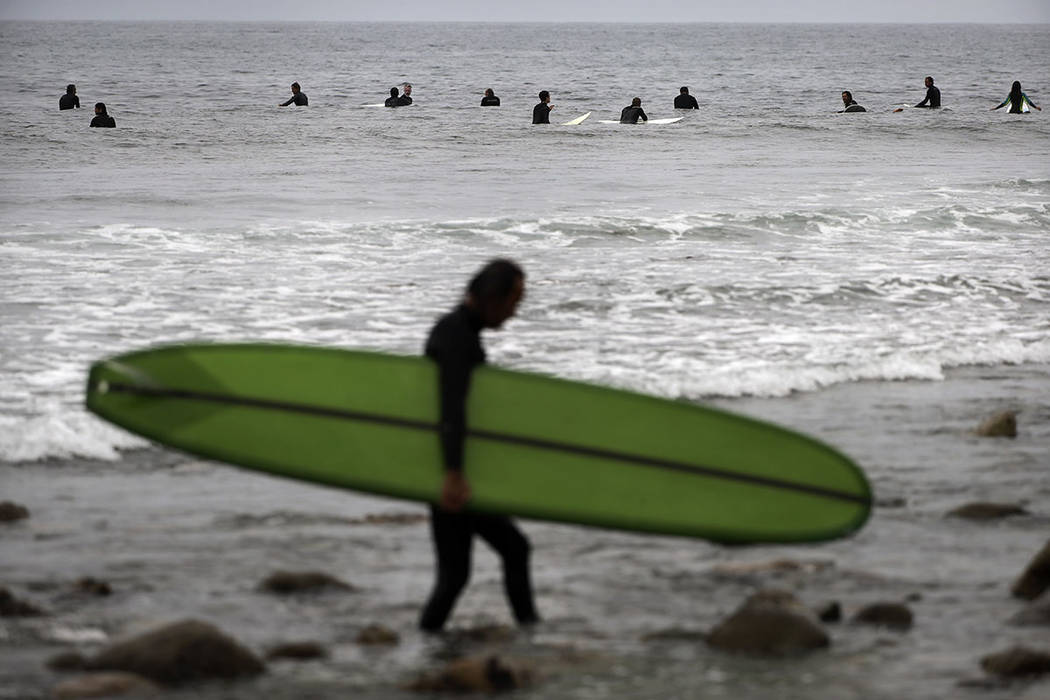 Hiroshi Konishi, foreground, walks out of the ocean after surfing as other surfers wait for waves in Malibu, Calif., in 2016.  (AP Photo/Jae C. Hong, file)