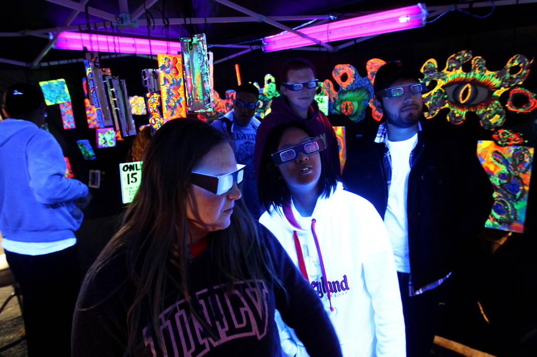 Natalie Rea, from left, Emerald Liu, Cody Hennessy and Victor Chavez check out 3D art at the Partners and Paint booth during First Friday in downtown Las Vegas' arts district Friday, March 2, 2018 ...