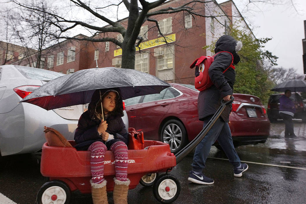 Astrid Fernandez gives her daughter Hailie a ride through the rain on the way to school, Friday, March 2, 2018, in the Brooklyn borough of New York. Rain and high winds are expected Friday in New  ...