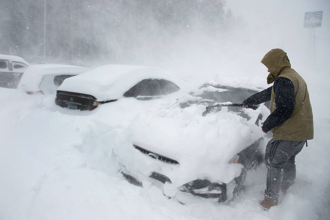 Heavy winds blow snow as Ryan Foster, 25, scrapes snow from his car in the parking lot where he lives at the Donner Summit Lodge in Norden on Thursday, March 1, 2018, near Donner Summit, Calif. (R ...