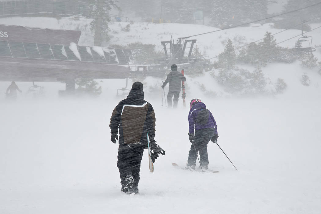 A snowboarder and pair of skiers make their way through gusts of wind to a lift Thursday, March 1, 2018, at the Northstar California resort in Truckee, Calif.  (Northstar California via AP)