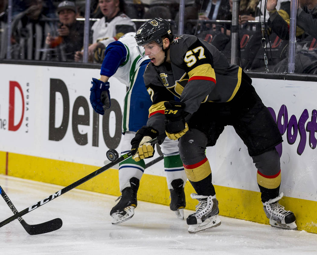 Golden Knights left wing David Perron (57) and Vancouver Canucks defenseman Troy Stecher (51) battle for the puck during the third period of an NHL hockey game at T-Mobile Arena in Las Vegas on Fr ...