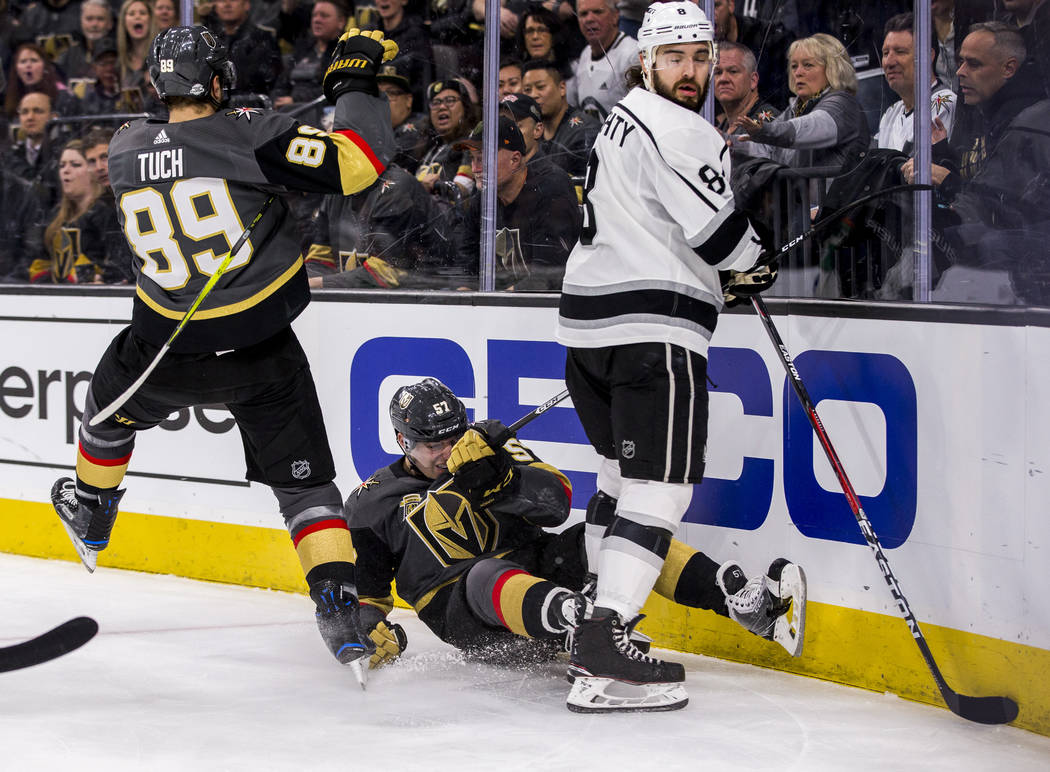 Vegas Golden Knights left wing David Perron (57), Vegas Golden Knights right wing Alex Tuch (89) and Los Angeles Kings defenseman Drew Doughty (8) get tangled up during the first period of an NHL  ...