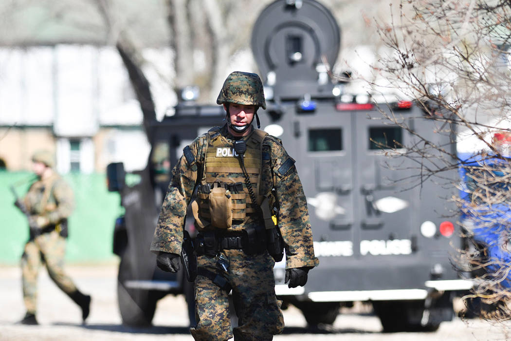 Law enforcement officers search a wooded area for a suspect involved in a shooting at a Central Michigan University residence hall on Friday, March 2, 2018 in Mt. Pleasant, Mich.  Two people who w ...