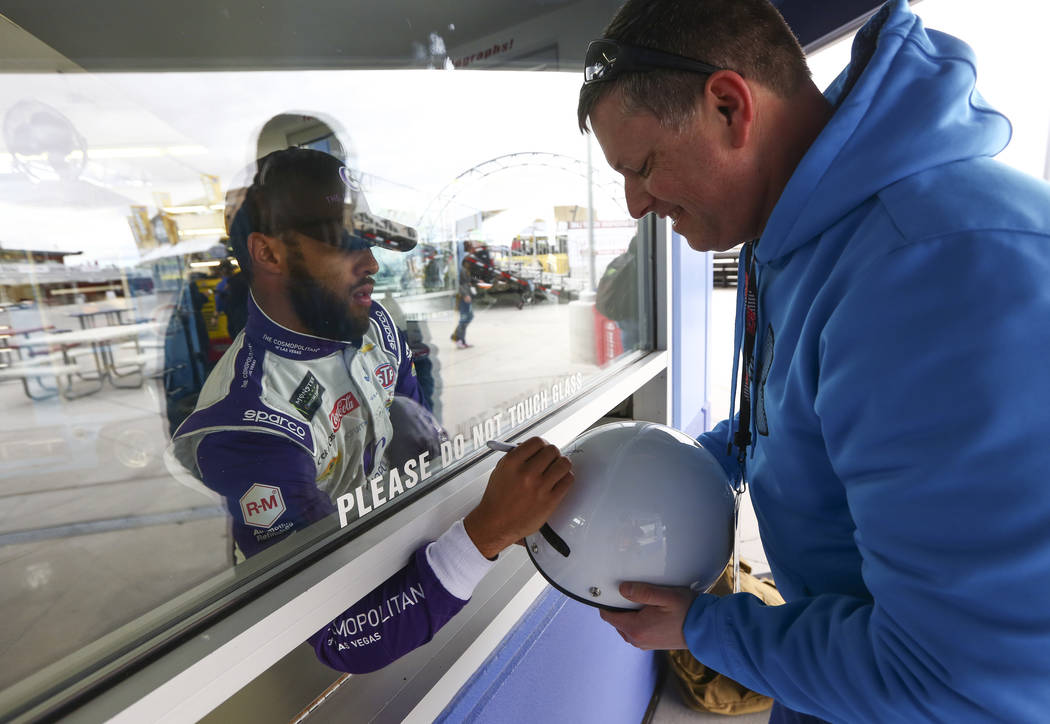 Monster Energy NASCAR Cup Series driver Darrell Wallace Jr. (43) signs a helmet for Jeff Babineau of Nova Scotia, Canada at the Las Vegas Motor Speedway in Las Vegas on Saturday, March 3, 2018. Ch ...
