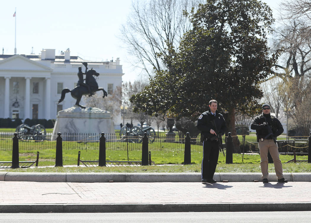 Law enforcement officers at Lafayette Park across from the White House in Washington, take up positions as they close the area to pedestrian traffic, Saturday, March 3, 2018.    The Secret Service ...