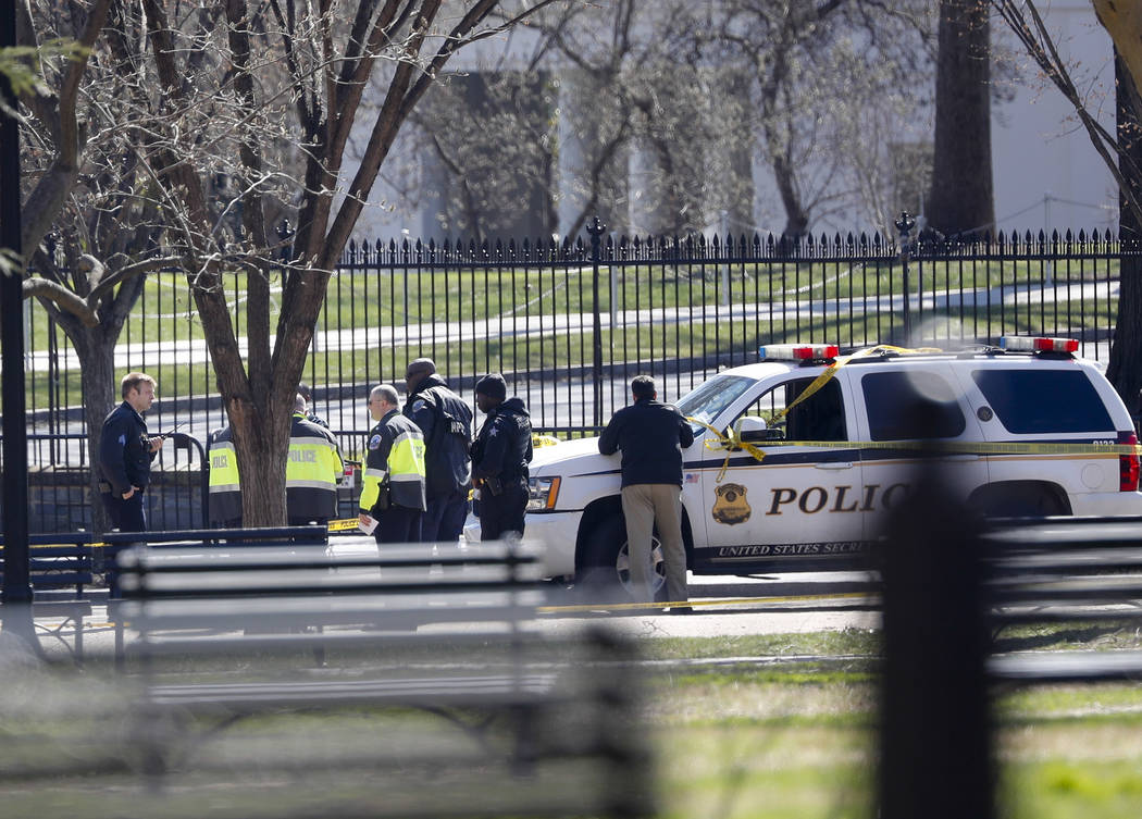 Law enforcement officers gather infront of the White House in Washington, Saturday, March 3, 2018.    The Secret Service says a man shot himself outside the White House, and medical personnel are  ...